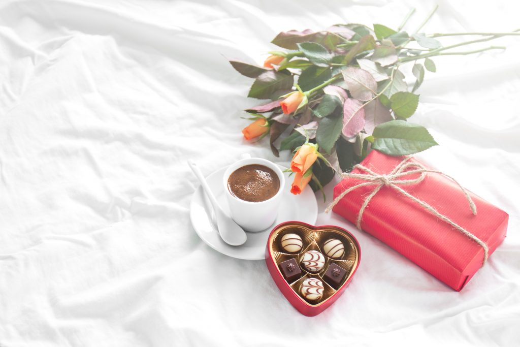 Beautiful colorful pretty gift or present in a natural paper with chocolate pralines, coffee and fresh roses on a bed. Holiday, valentine's day, birthday or surprise concept