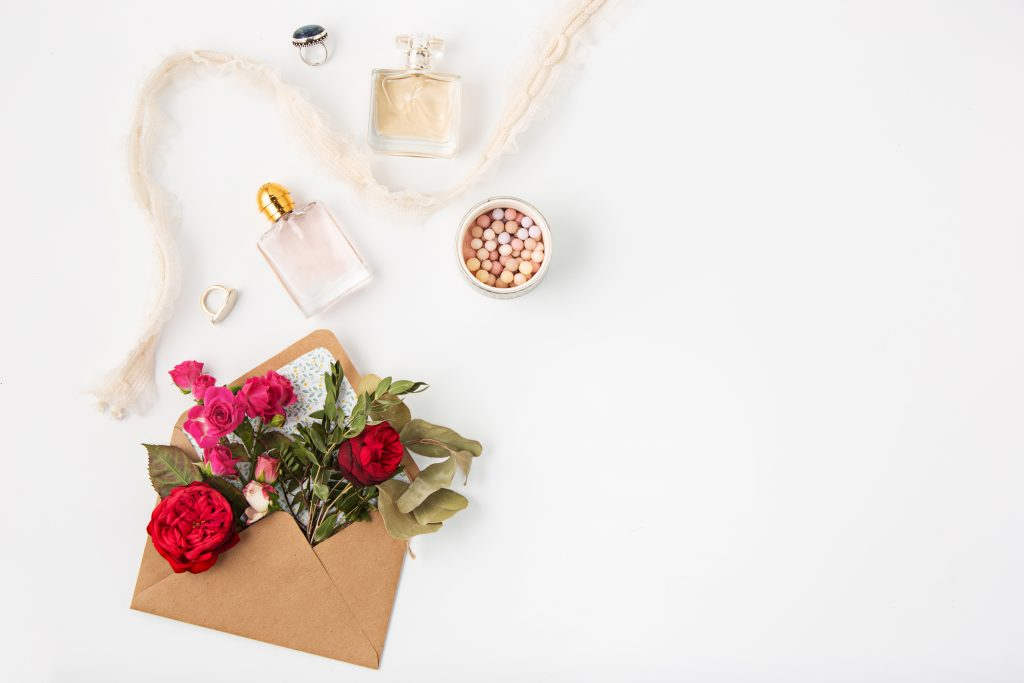 Love or valentine's day concept. Red beautiful roses in envelopen on a white background. Top view